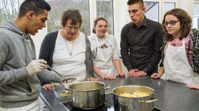 Saip Berisa erhitzt die russischen Teigtaschen. Mitschüler und Lehrerinnen lassen sich das Rezept erklären. Foto. SMMP/Bock