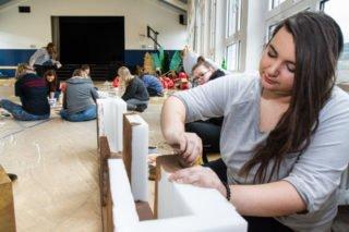 Denise Bunse bemalt die Mauer-Elemente: So wird die Hartschaum-Verpackung der neuen digitalen Tafeln recycelt. Foto: SMMP/Ulrich Bock